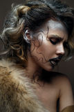 Beautiful girl with creative make-up with gold and silver and curls. Model with fur and bright dark lips. Beauty face. The image i. N Gatsby style. The photo was Stock Photos