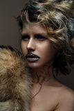 Beautiful girl with creative make-up with gold and silver and curls. Model with fur and bright dark lips. Beauty face. The image i Stock Photo