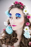 Beautiful girl with creative make-up and hairstyle with flowers Stock Image