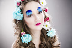 Beautiful girl with creative make-up and hairstyle with flowers Royalty Free Stock Photos