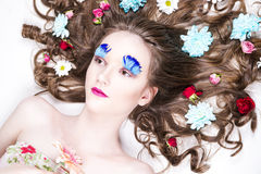 Beautiful girl with creative make-up and hairstyle with flowers Royalty Free Stock Photo