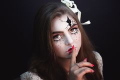 Briken doll. Beautiful girl with creative make-up for the Halloween party. Bright colors faceart, pink lips, stylish hair dress design. Conceptual art broken Stock Image