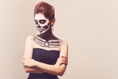 Beautiful girl with creative make-up for the Halloween party. Beautiful woman with make-up skeleton Stock Photo