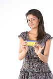 Beautiful girl with credit card. Teenage Girl with gold color credit card over white background Royalty Free Stock Photos