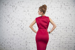 Beautiful  girl in crimson  dress with back Royalty Free Stock Photos
