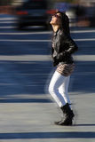 Beautiful Girl Crossing the Street (2). A lovely dark-haired teenage girl with a bright, warm smile walks across the road on a sunny day.  A motion effect is Stock Images