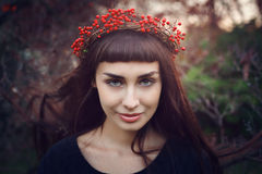 Beautiful girl with crown of red berries Stock Image