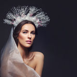 Beautiful girl in crystal crown and veil. Beautiful young brunette woman in crystal crown and white veil on black background. Romantic beauty look. Copy space Royalty Free Stock Photography