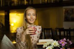 Beautiful girl with a cup reading a book Stock Photography