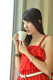 Beautiful girl with cup of coffee looking out Royalty Free Stock Photos
