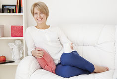 Beautiful girl with a cup on the couch Royalty Free Stock Photos