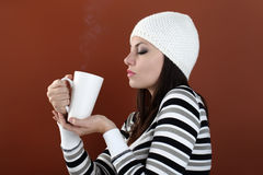 Beautiful girl with cup in hands to keep warm drink Royalty Free Stock Images