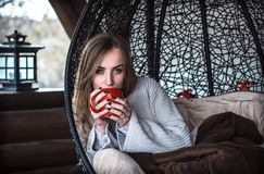 Girl with a Cup of tea in a comfortable chair. Beautiful girl with Cup of tea sitting in a comfortable chair Royalty Free Stock Photos