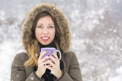 Beautiful girl with cup of tea on snowy day Stock Image