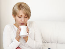 Beautiful girl with a cup on a white couch Royalty Free Stock Photo