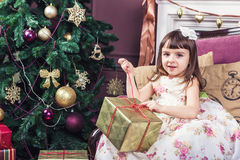 Beautiful girl with curiosity opens a box with a gift surprise. Royalty Free Stock Photography