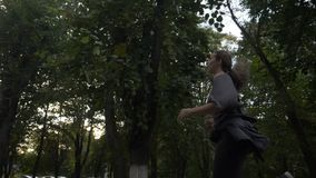 Beautiful girl with curled long hair running near the trees in park to loose extra weight in slow motion -. Beautiful girl with curled long hair running near the stock footage
