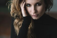 Beautiful girl with curls and full lips in a black turtleneck. Close-up portrait.