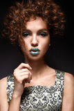 Beautiful girl with curls and green glitter on the eyelids and lips. Model woman with beautiful make up and curly hairstyle. Beauty face. The photo was taken Stock Image