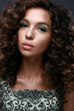 Beautiful girl with curls and green glitter on the eyelids. Model woman with beautiful make up and curly hairstyle. Beauty face. The photo was taken in a Stock Photography