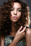 Beautiful girl with curls and green glitter on the eyelids. Model woman with beautiful make up and curly hairstyle. Stock Photo