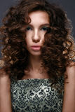Beautiful girl with curls and green glitter on the eyelids. Model woman with beautiful make up and curly hairstyle. Stock Photos