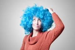 Beautiful girl with curly blue wig and turtleneck. On colorful background Royalty Free Stock Image