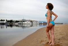 The beautiful girl with a curly hair in a blue bikini on a beach Royalty Free Stock Image