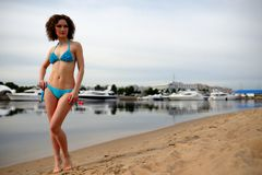 The beautiful girl with a curly hair in a blue bikini on a beach Royalty Free Stock Photography