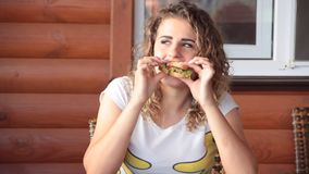 Beautiful girl curly hair eating a summer sandwich. Sunny cafe stock video footage