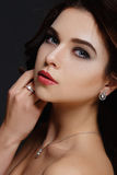 Beautiful girl with curly hair and evening make-up. Model with jewelry and luxurious lips Stock Photo