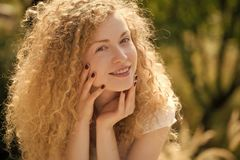 Beautiful girl with curly hair. Happy woman outdoor. Beautiful girl with curly hair. Portrait of one beautiful positive charming blonde young smiling lady with stock photos