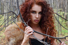 Beautiful girl with curly hair poses among tree branches Stock Photo