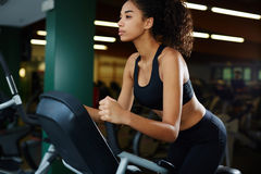 Beautiful girl with curly hair in a short sports top riding on spin bike Stock Photo