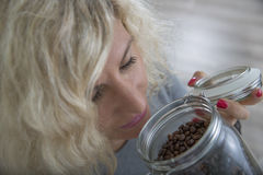 Beautiful girl with curly hair is smelling coffee beans in glass pot Royalty Free Stock Image
