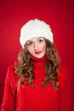 Beautiful girl with curly hair wearing warm hat and red sweater Stock Photo
