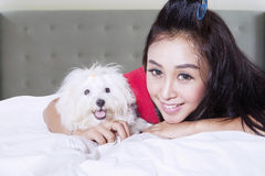 Beautiful girl with cute puppy. Image of Beautiful girl with cute puppy while lying on the bed Stock Images