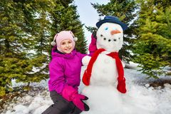 Beautiful girl and cute snowman with red scarf Royalty Free Stock Photos