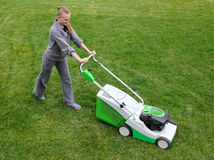 Beautiful girl cuts the lawn Stock Photo