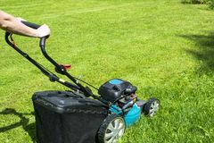 Beautiful girl cuts the lawn. Mowing lawns. Lawn mower on green grass. mower grass equipment. mowing gardener care work tool Royalty Free Stock Photos