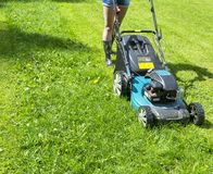 Beautiful girl cuts the lawn. Mowing lawns. Lawn mower on green grass. mower grass equipment. mowing gardener care work tool Royalty Free Stock Images