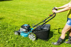 Beautiful girl cuts the lawn, Mowing lawns, Lawn mower on green grass, mower grass equipment, mowing gardener care work tool Royalty Free Stock Image