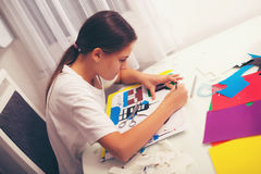Beautiful girl cutting paper on the art lesson class. Royalty Free Stock Images