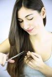 Beautiful girl cutting split ends of long hair Stock Photo