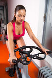 Beautiful girl cycling in the gym. Beautiful fit girl exercising on the bicycle in the gym Stock Images