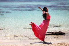 Beautiful girl dancing on the beach. Beautiful young woman dancing in coral - pink long dress  on the exotic beach of Elafonisi Crete Greece Stock Images