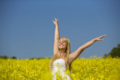 A beautiful girl dancing in a field of yellow flowers Royalty Free Stock Photo