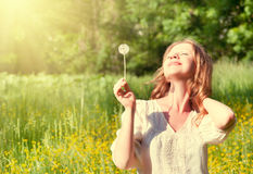 Beautiful girl with dandelion enjoying summer sun. Beautiful girl with dandelion enjoying the summer sun outdoors in the park Stock Image