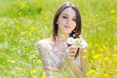 Beautiful girl with dandelion in yellow field Royalty Free Stock Image