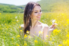 Beautiful girl with dandelion in yellow field Royalty Free Stock Photography